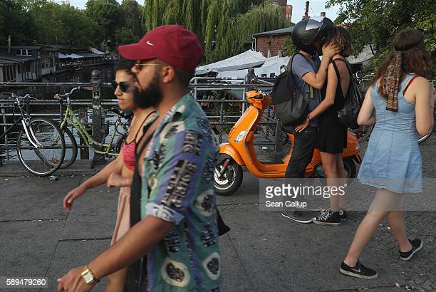 A couple kiss as people walk by on a bridge over a branch of the Landwehr Canal in Kreuzberg district on a warm summer evening on July 10 2016 in...