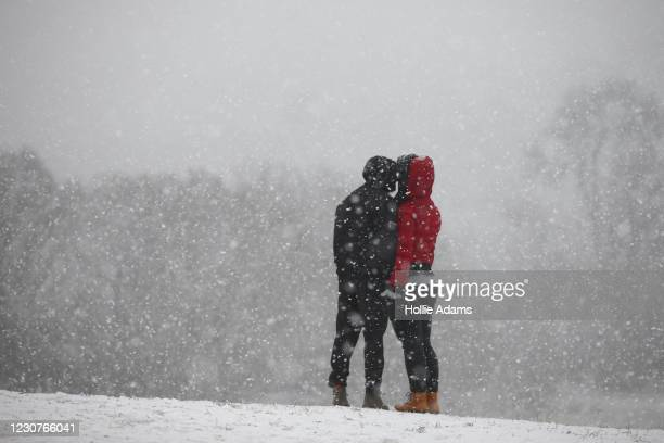Couple kiss as snow falls on Hampstead Heath on January 24, 2021 in London, United Kingdom. Parts of the country saw snow and icy conditions as...