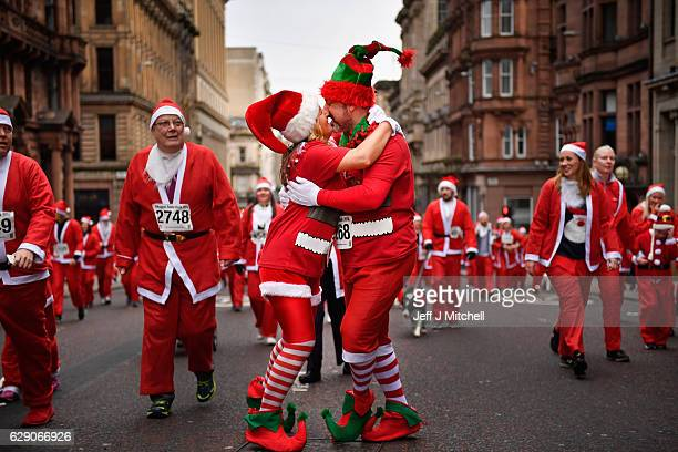 A couple kiss as they joined over seven thousands of members of the public dressed as Santas make their way up St Vincent Street on December 11 2016...