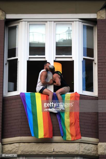 A couple kiss as they sit at their window as crowds supporting the Same Sex marriage Survey march down Oxford St and into the city whilst a same sex...