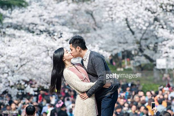 Couple kiss as they visit the avenue to look at the cherry blossom at Wuhan University on March 21, 2015 in Wuhan, Hubei province of China. The 200...