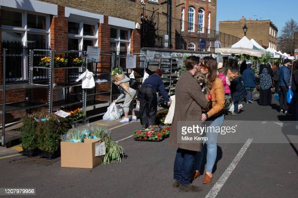 Couple kiss at Columbia Road flower market on Mother's Day and it's last open Sunday for a while due to Covid19 on what would normally be a busy...