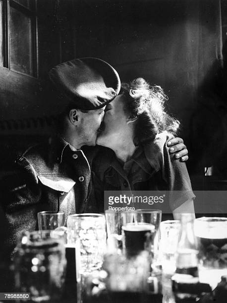Couple kiss at the corner table of a pub as they take part in Victory in Europe Day celebrations to mark the end of European conflict in World War...