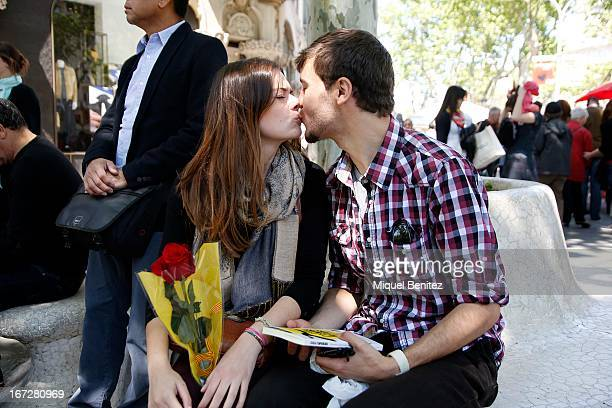Couple kiss during 'Sant Jordi's day ' or 'Saint George's day' when traditionally Catalan men give women roses and women give men a book on April 23,...