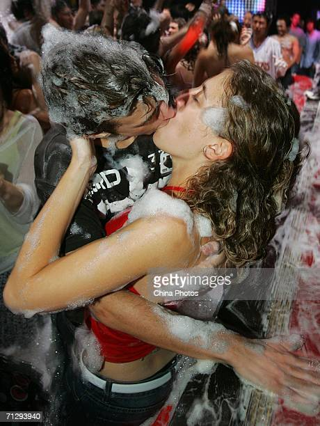 A couple kiss during the Foam Party at the Rojam Disco on June 24 2006 in Shanghai China Foam Parties during which participants are lathered up with...