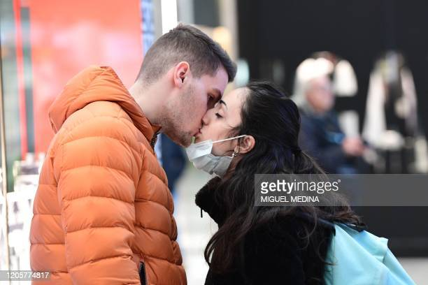 Couple kiss in Milano Centrale railway station in Milan on March 8 after millions of people were placed under forced quarantine in northern Italy as...