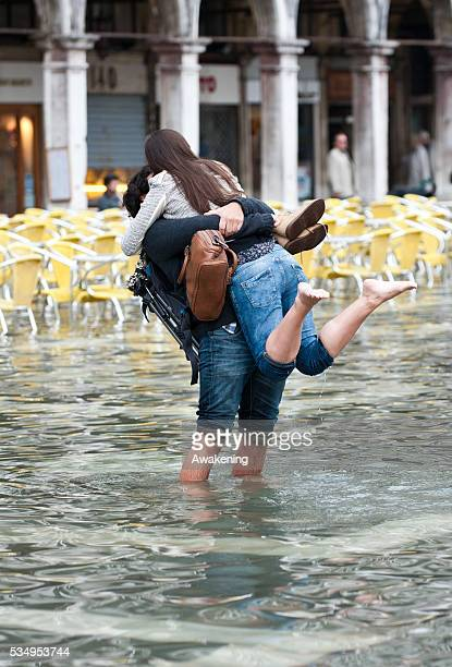 A couple kiss in St Mark's Square during today first high tide of the season in Venice with water reaching the level at sea of 110 centimetres above...