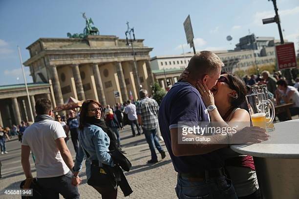 A couple kiss near the Brandenburg Gate on German Unity Day on October 3 2014 in Berlin Germany Germany is celebrating the 24th anniversary of the...