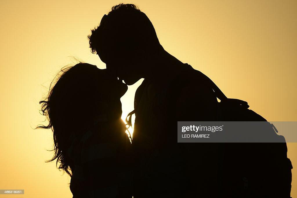A couple kiss near the shore of El Yaque Beach, Nueva Esparta state, Margarita Island, Venezuela on January 31, 2014. AFP PHOTO/Leo RAMIREZ