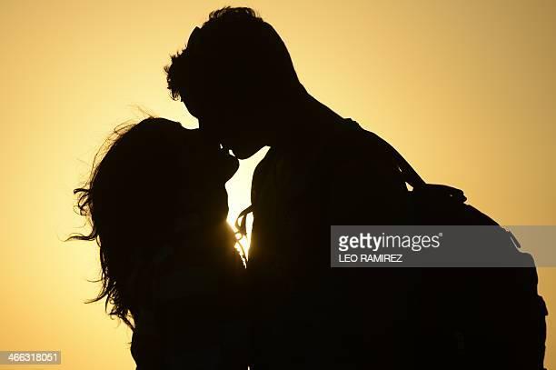 A couple kiss near the shore of El Yaque Beach Nueva Esparta state Margarita Island Venezuela on January 31 2014 AFP PHOTO/Leo RAMIREZ