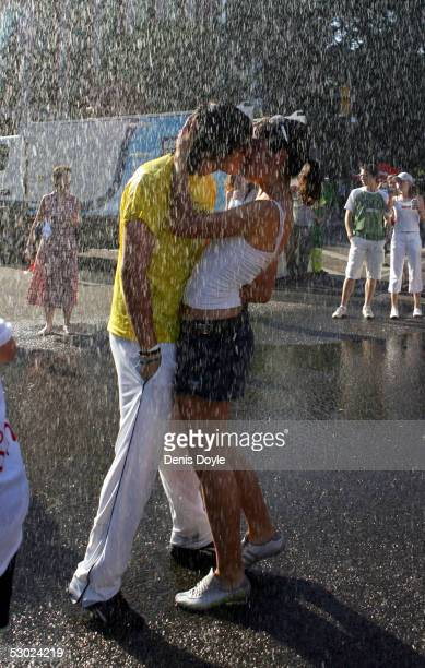 A couple kiss while cooling down with spray from a fire hose during a street party to promote Madrid's 2012 Olympic bid on June 5 2005 in Madrid Spain