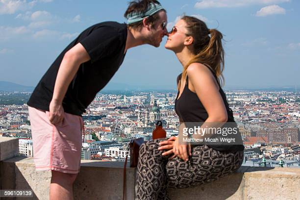 A couple kiss with a scenic spot behind.