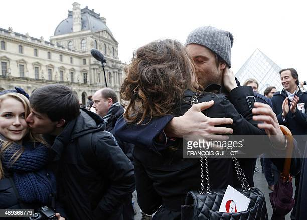 A couple kisses during a flashmob near the Louvre Pyramid in Paris on February 14 to mark the launch of the website Wikilovecom an online...