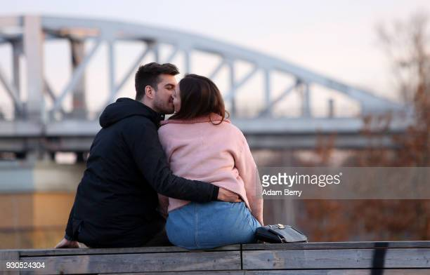 A couple kisses in a park on March 11 2018 in Berlin Germany A high temperature of 16 degrees Celsius brought residents and tourists outside to enjoy...