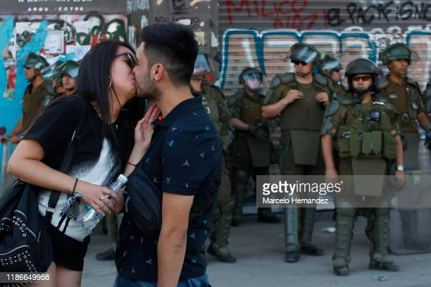 A couple kisses in front of the police during protests against president Sebastian Piñera at Plaza Italia on December 5 2019 in Santiago Chile...