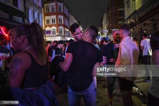 Couple kisses in heavy crowds in Soho on July 4, 2020 in London, United Kingdom. The UK Government announced that Pubs, Hotels and Restaurants can...