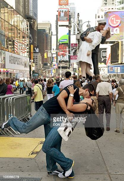 Couple kisses in Times Square near the a sculpture at the site of the historic LIFE Magazine cover photograph, of an unidentified sailor kissing...