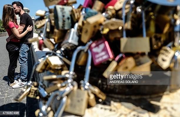 A couple kisses near a lamppost bearing 'love padlocks' on the Ponte Milvio in Rome on May 29 2015 Inspired by the romantic protagonists in Federico...