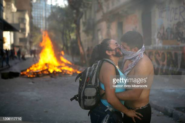 A couple kisses next to a burning barricade during protests as part of the International Women's Day at Plaza Baquedano on March 8 2020 in Santiago...