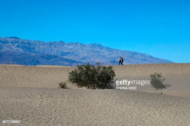 A couple kisses on the Mesquite Flat Sand Dunes in Death Valley National Park in Death Valley California on February 14 2017 / AFP PHOTO / RHONA WISE