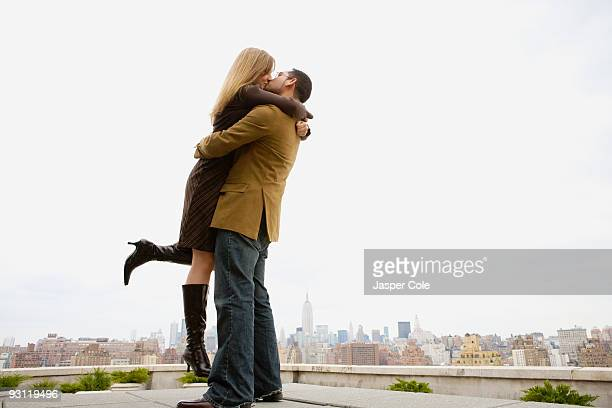 Couple kissing and hugging on rooftop