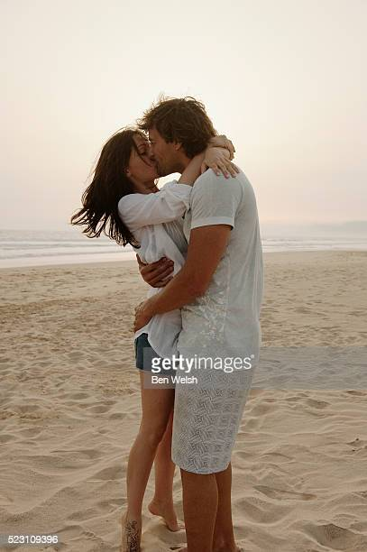 couple kissing at beach - mid adult men foto e immagini stock