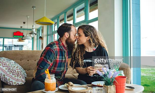 Couple kissing at breakfast in cafe