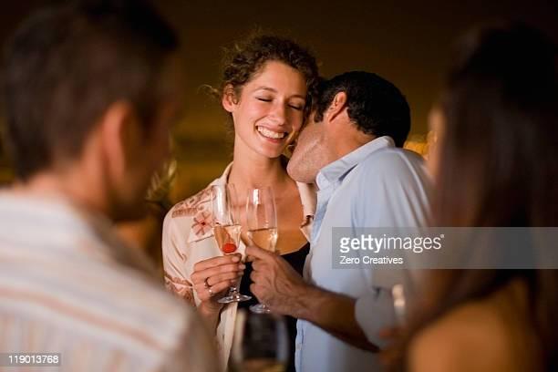 Couple kissing at party at night
