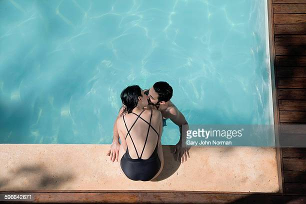 Couple kissing at poolside at their apartment.