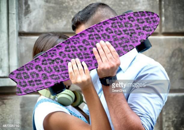 Couple kissing Behind a Purple Skatboard