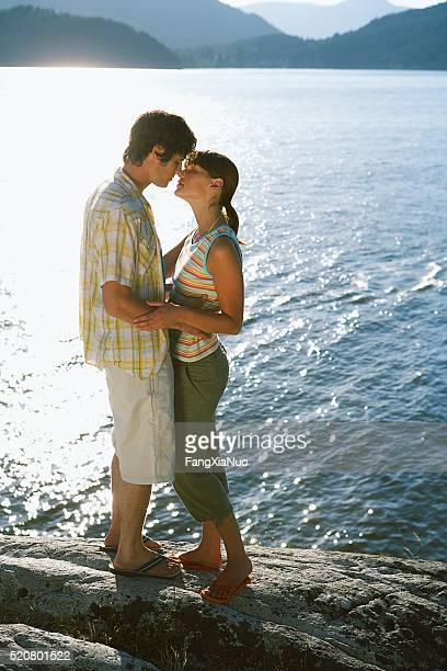 Couple kissing beside a lake