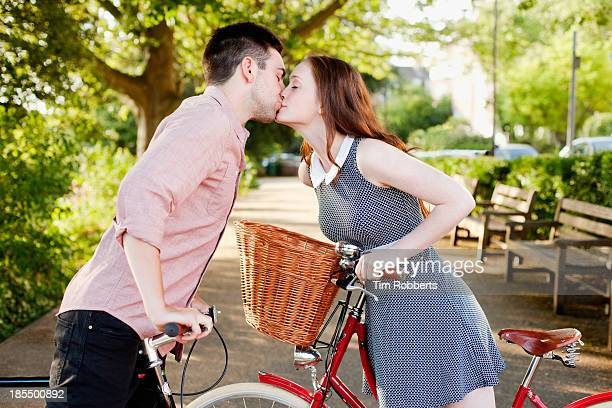 couple kissing between bikes - sleeve stock pictures, royalty-free photos & images
