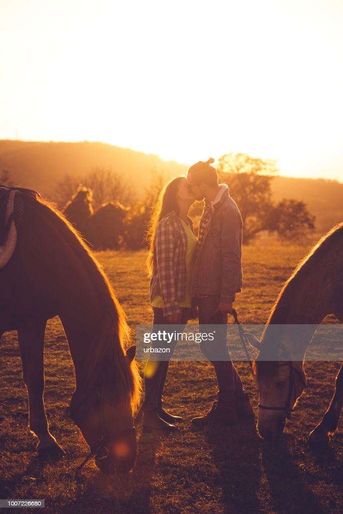 Couple Kissing Between Two Horses At Sunset High Res Stock Photo Getty Images