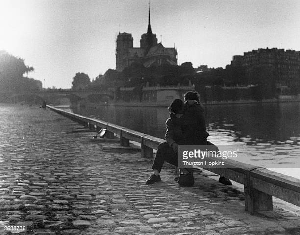 A couple kissing by the River Seine in Paris with Notre Dame cathedral in the background Original Publication Picture Post 6002 Paris Pride pub 1952