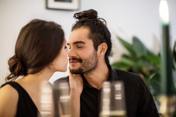couple kissing during dinner party at home - couples romance stock pictures, royalty-free photos & images