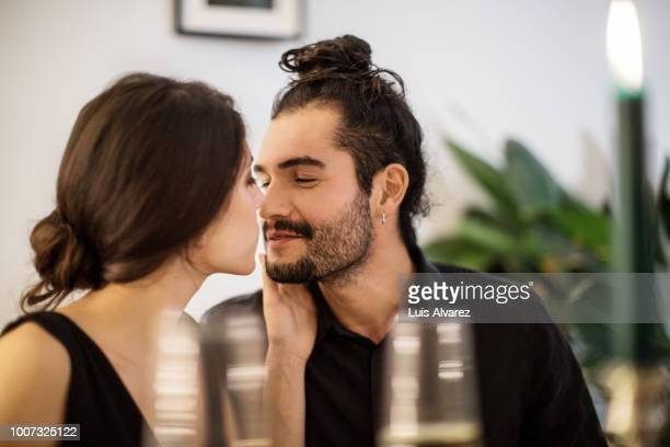 couple kissing during dinner party at home - dating stock-fotos und bilder