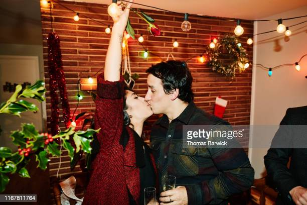 couple kissing during holiday party with friends - love stock pictures, royalty-free photos & images