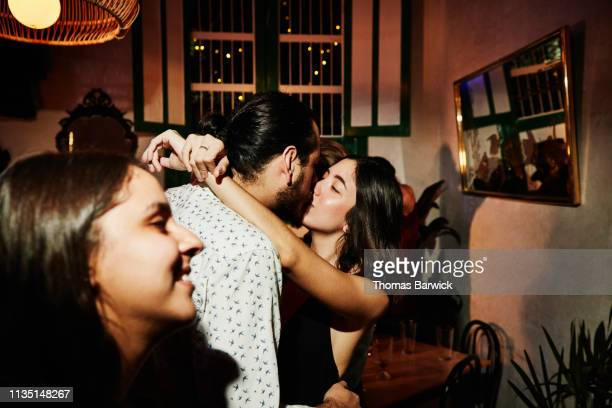 couple kissing during party with friends in night club - kissing stock pictures, royalty-free photos & images