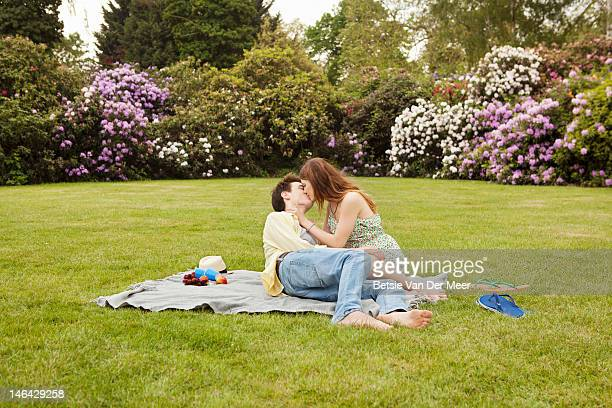 couple kissing, having picnic in park.
