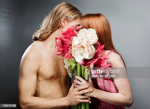 couple kissing, hiding behind bouquet of flowers.