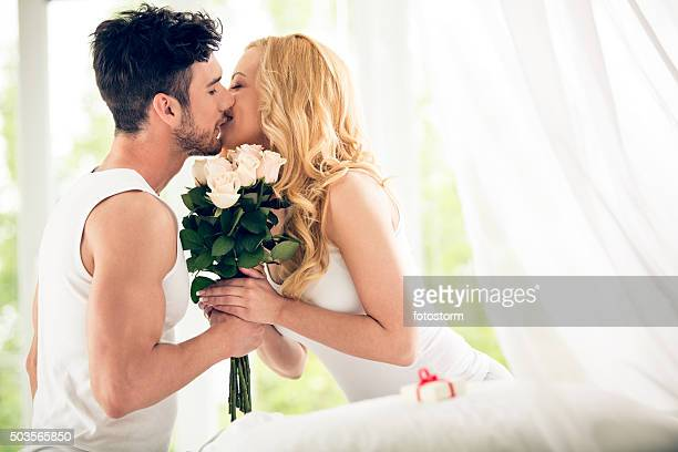 Couple kissing, holding flowers
