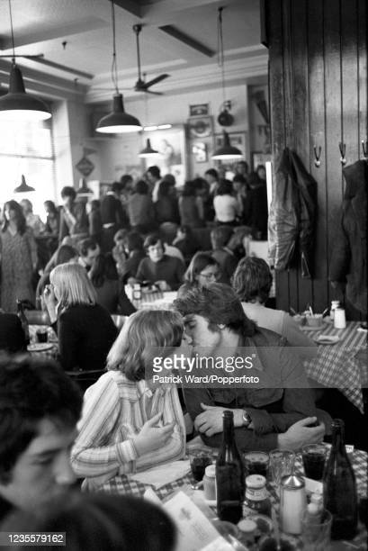 Couple kissing in a busy London cafe, circa 1975.