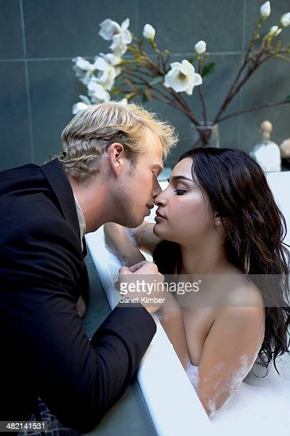 couple kissing in bubble bath - couple and kiss and bathroom stock photos and pictures