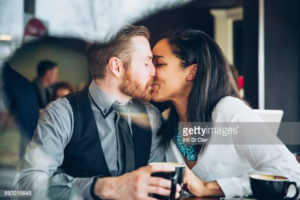 couple kissing in cafe - black women kissing white men stock pictures, royalty-free photos & images