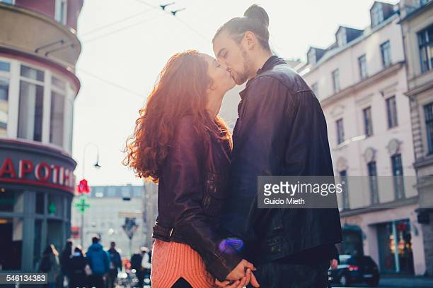 Couple kissing in city.