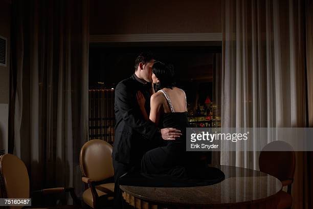 Couple kissing in dark room, woman sitting on table in dark room, night