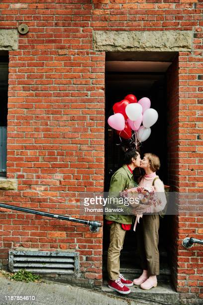 couple kissing in doorway while on valentines day date - valentines day stock pictures, royalty-free photos & images