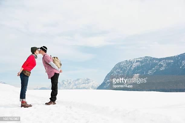 couple kissing in front alps - beugen oder biegen stock-fotos und bilder