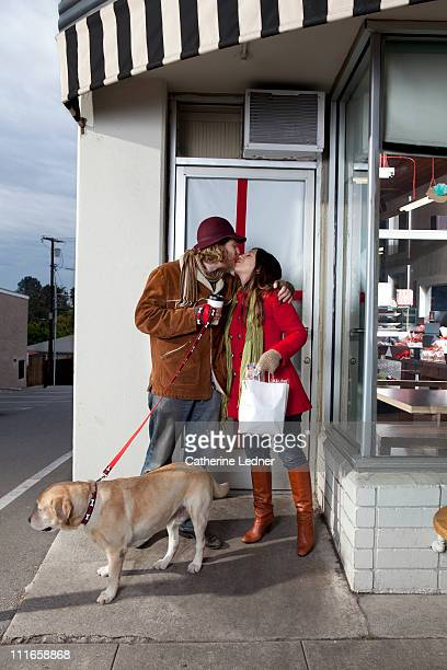 couple kissing in front of a store with their dog - ブーツイン ストックフォトと画像