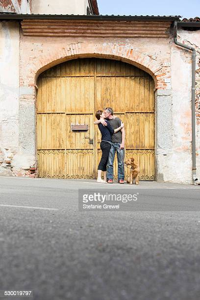 Couple kissing in front of building entrance on street, Suno, Novara, Italy